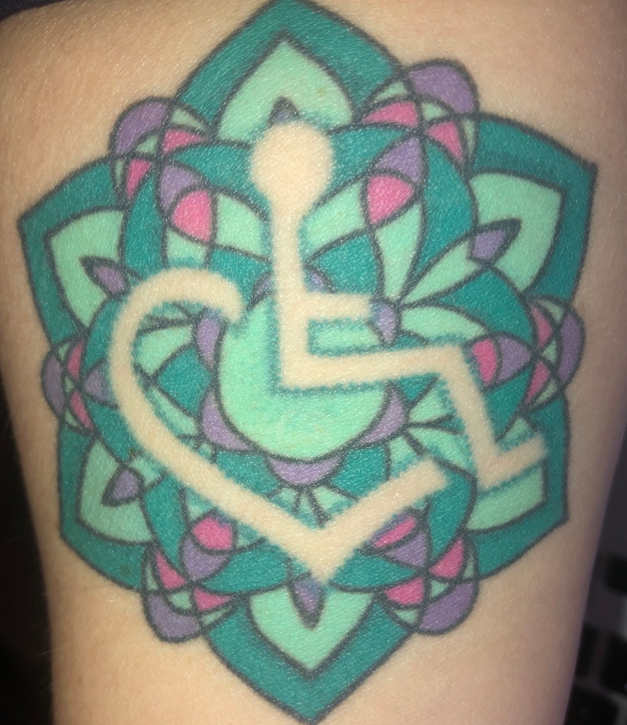 An image of my beautiful disability pride tattoo, which is a turquoise, purple, and pink geometrical design (à la stained glass) with a negative space wheelchair heart).  The wheelchair heart is the 3E Love design from Stevie Hopkins.